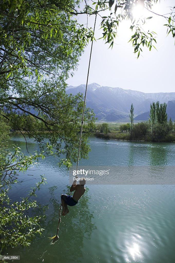lifestyle portrait of a male child as he swings out over a pond on a rope : Foto de stock