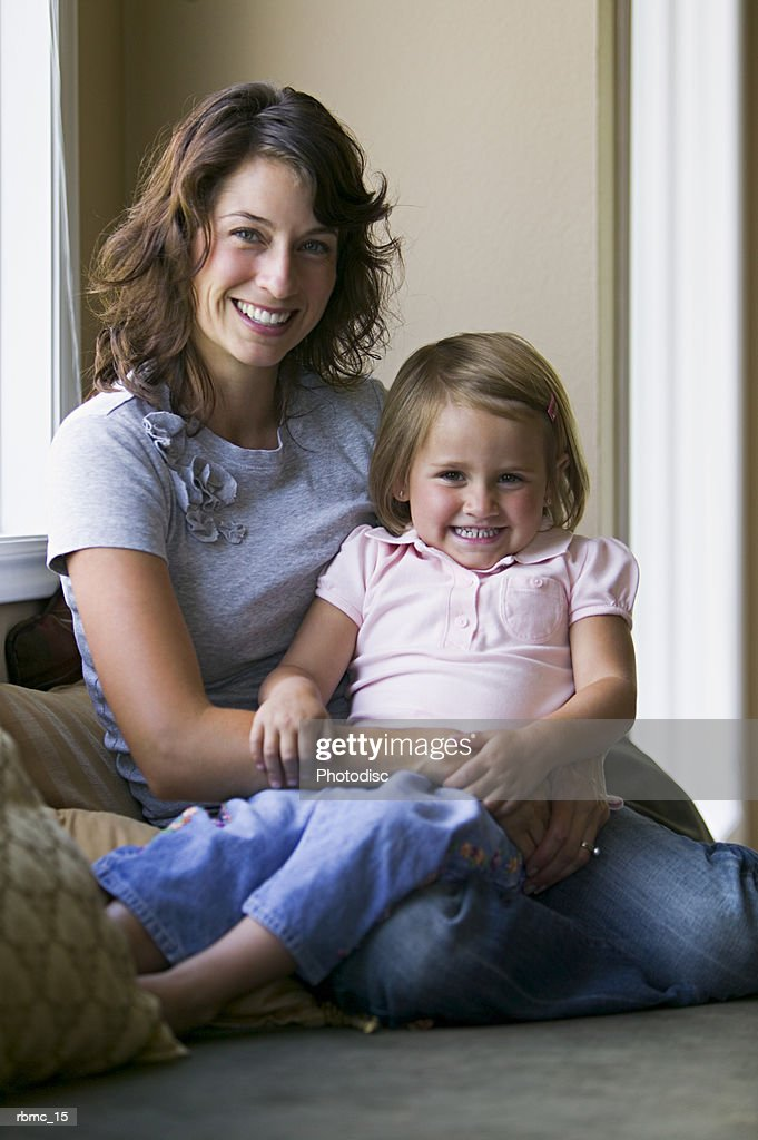 lifestyle portrait of a mother as she sits on a couch and holds her young daughter : ストックフォト