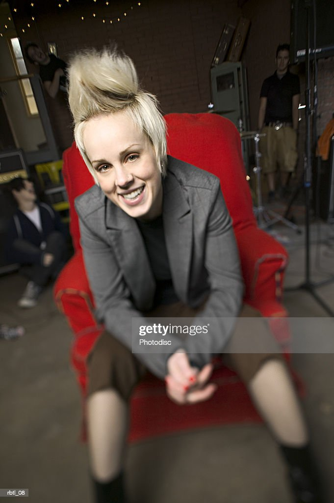 lifestyle portrait of a teenage blonde female as she sits in a chair with her friends behind her : Foto de stock