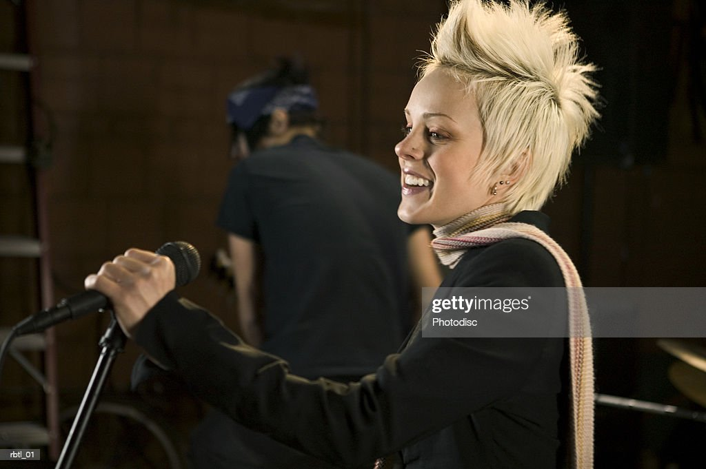 lifestyle portrait of a teenage blonde female as she stands at the microphone of her band : Foto de stock