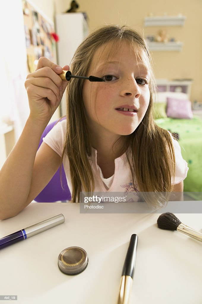 lifestyle portrait of a teenage female as she looks in the mirror to put on eye shadow : Foto de stock