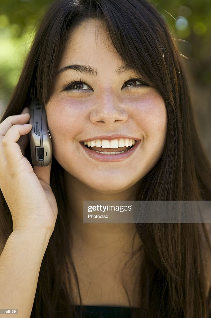 lifestyle portrait of a teenage female as she talks on a cell phone and smiles brightly : Foto de stock