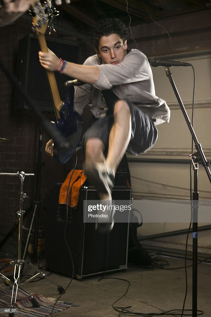 lifestyle portrait of a teenage male as he jumps up through the air while playing his guitar : Foto de stock