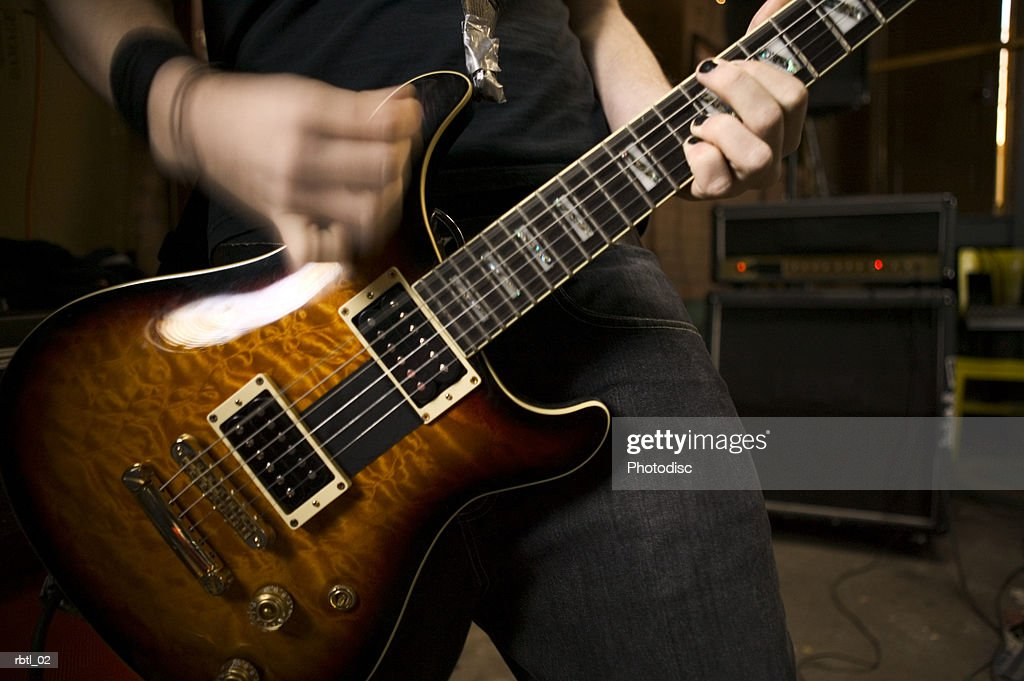 lifestyle portrait of a teenage male as he plays his electric guitar : Foto de stock