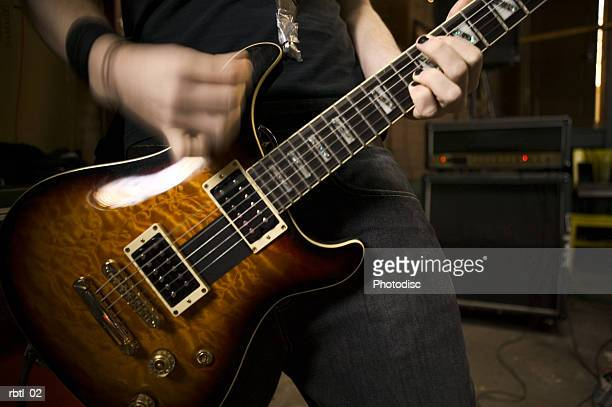lifestyle portrait of a teenage male as he plays his electric guitar