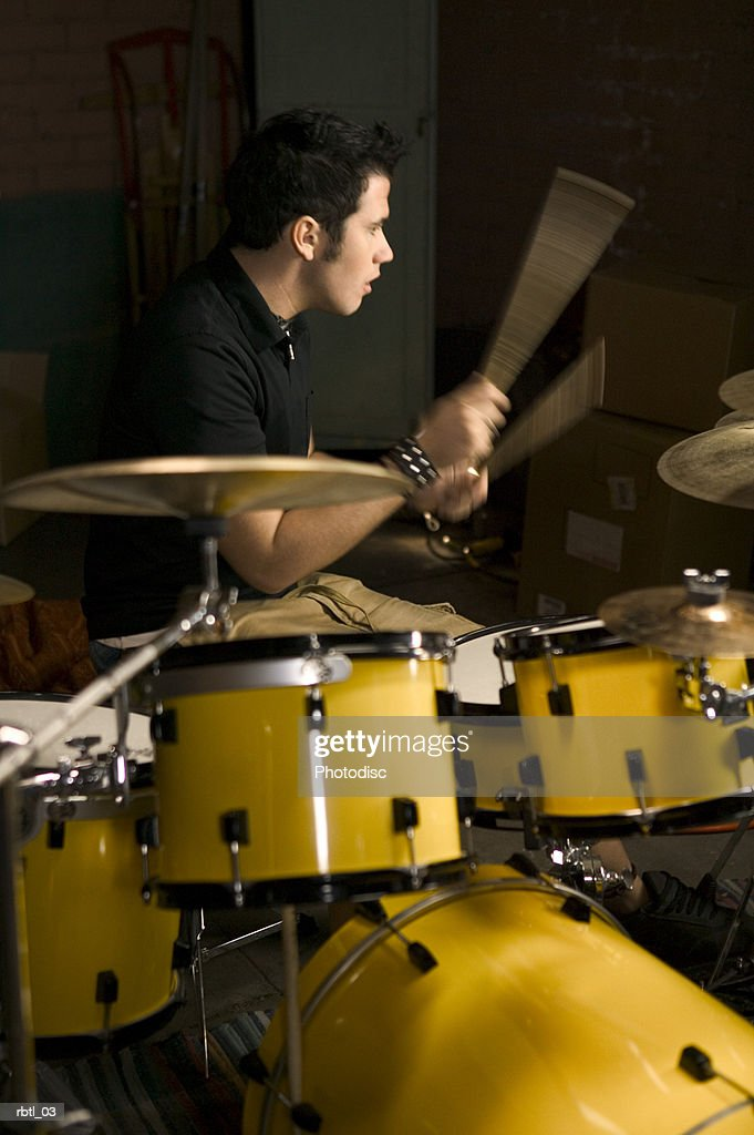 lifestyle portrait of a teenage male as he wildly plays the drums : Foto de stock