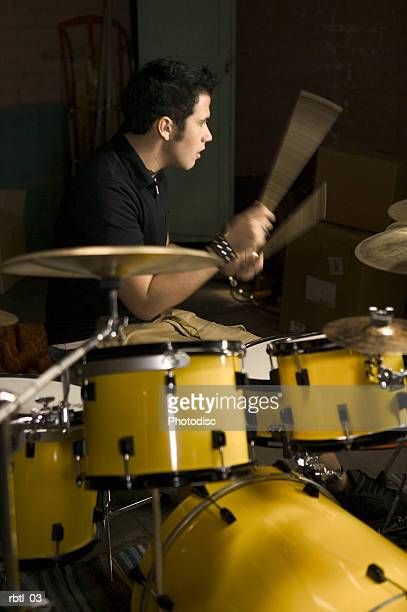 lifestyle portrait of a teenage male as he wildly plays the drums