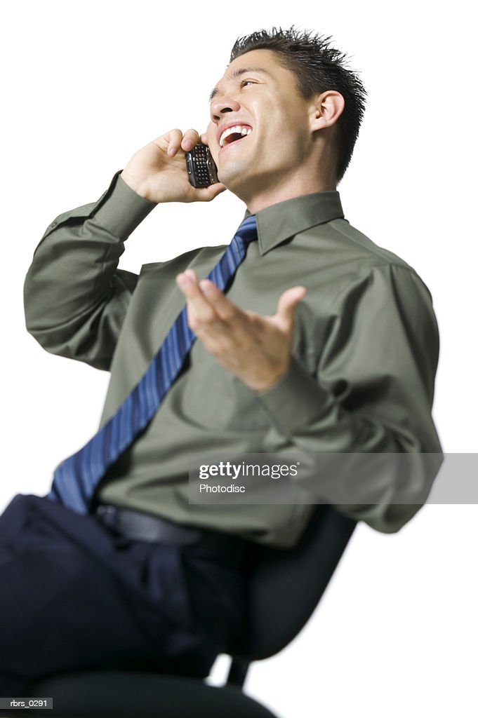 lifestyle portrait of a young adult business man as he leans back and chats on a cell phone : Foto de stock