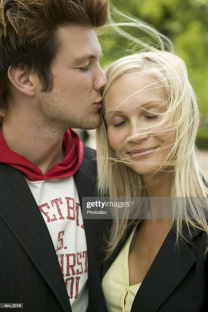 lifestyle portrait of a young adult couple as the man leans in and kisses his girlfriend : Foto de stock