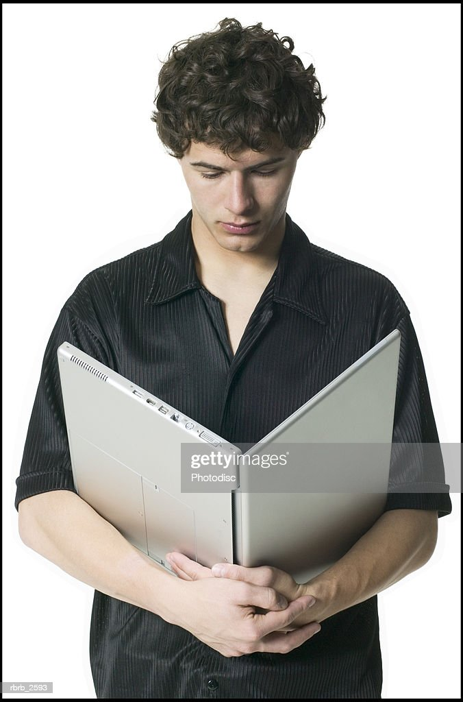 lifestyle portrait of a young adult male in a black shirt as he holds his laptop computer : Foto de stock