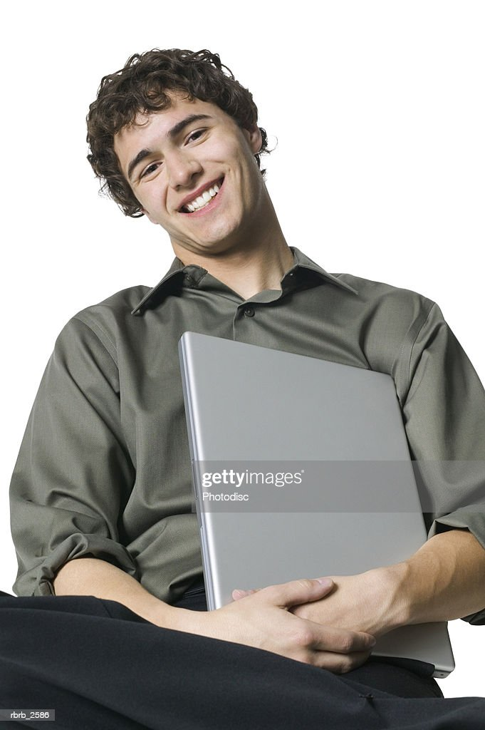 lifestyle portrait of a young adult male in a grey shirt as he holds his laptop computer : Foto de stock