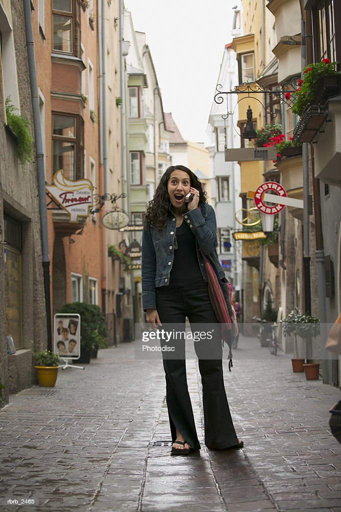lifestyle portrait of a young adult woman as she chats on her cell phone while visiting europe : Foto de stock