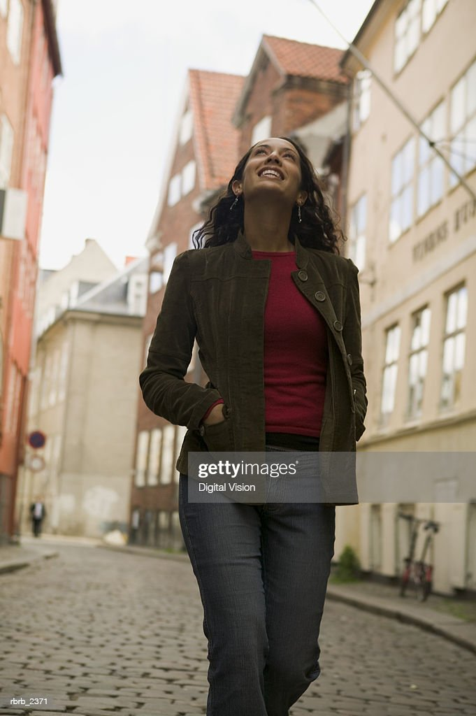 lifestyle portrait of a young adult woman as she goes out sightseeing while on vacation : Foto de stock