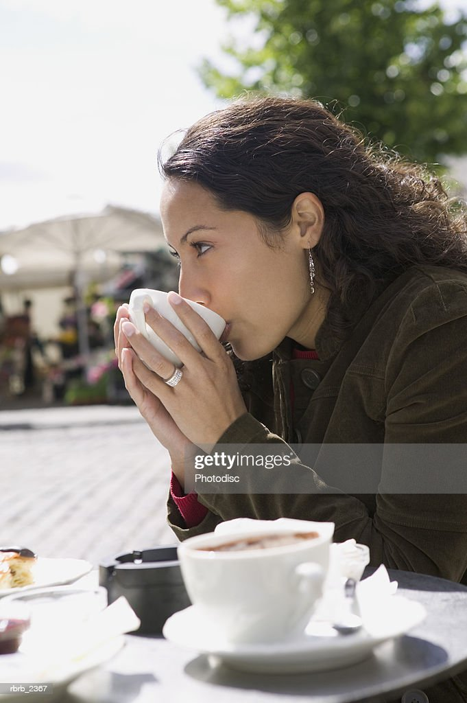 lifestyle portrait of a young adult woman as she sips from her cup at an outdoor cafe : Stock Photo