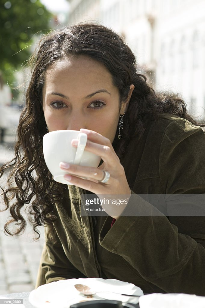 lifestyle portrait of a young adult woman as she sips from her cup at an outdoor cafe : Foto de stock