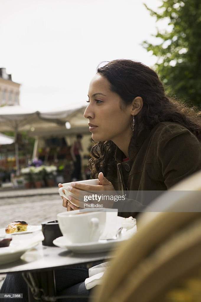 lifestyle portrait of a young adult woman as she sits at an outdoor cafe : Foto de stock