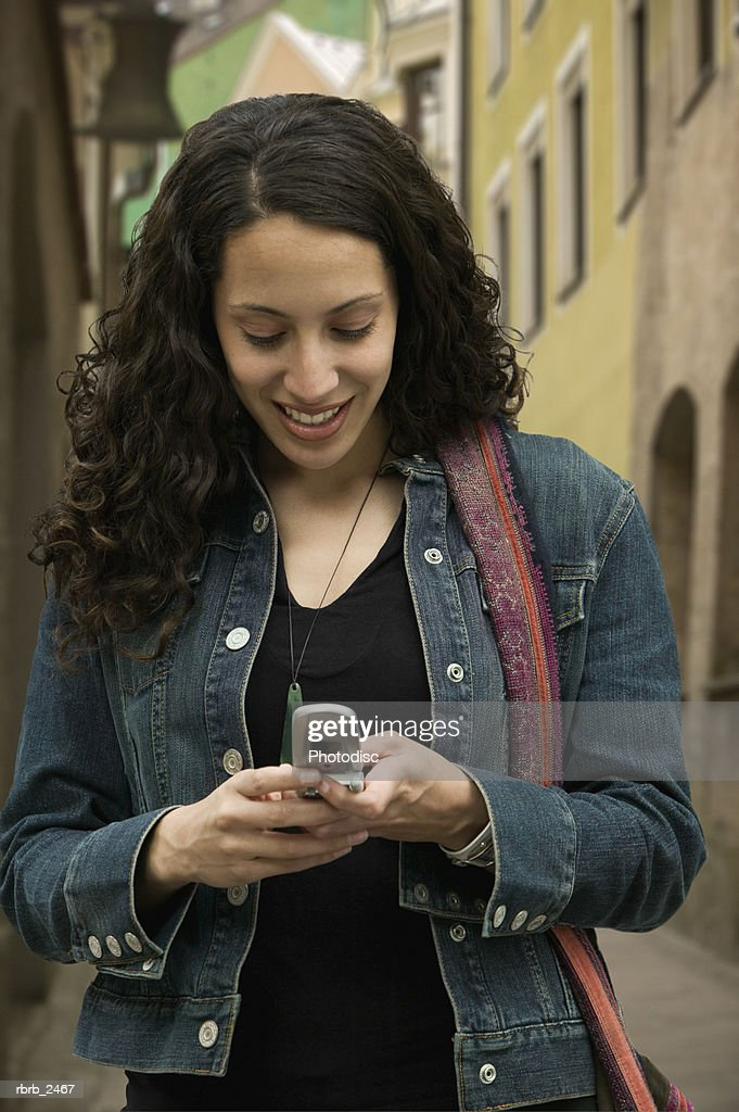 lifestyle portrait of a young adult woman as she uses her cell phone to send text messaging : Foto de stock