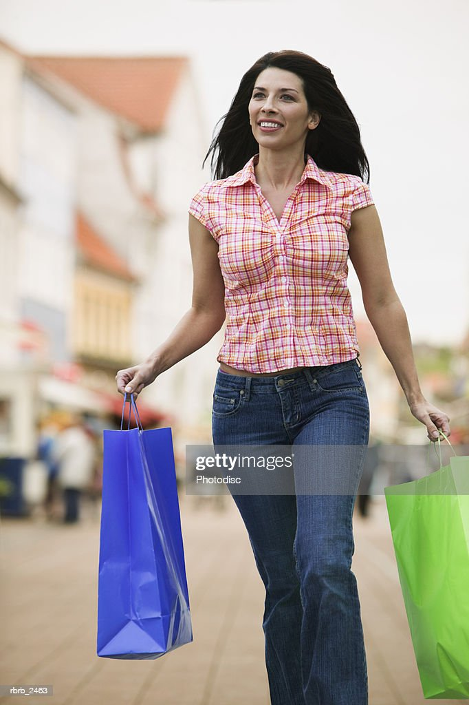 lifestyle portrait of a young adult woman as she walks through a plaza with shopping bags : Foto de stock