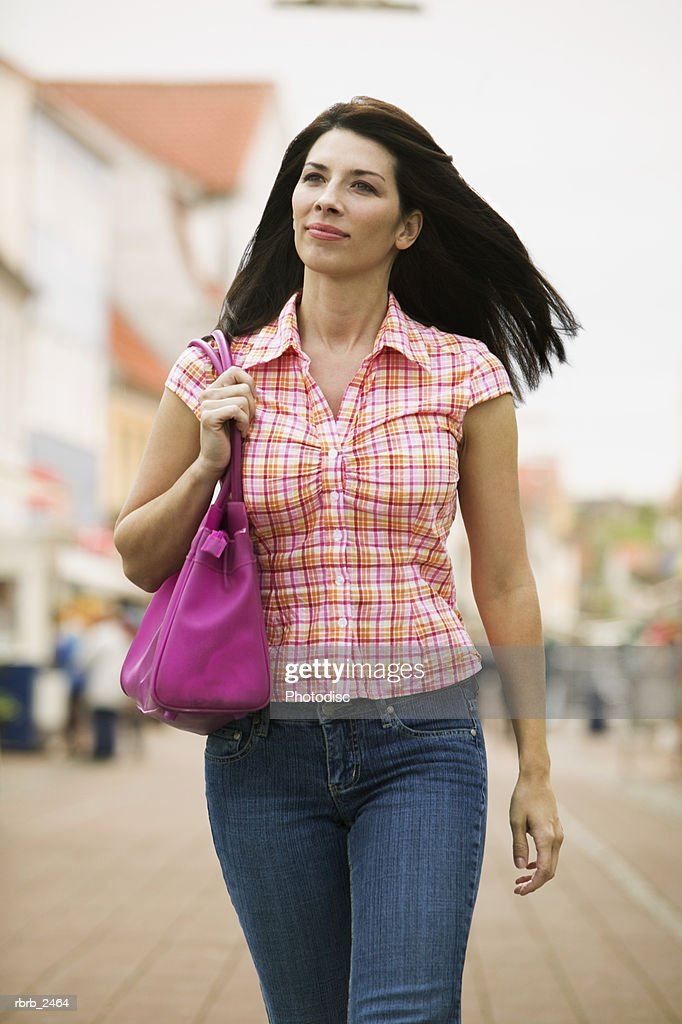 lifestyle portrait of a young adult woman as she walks through a plaza : Stockfoto