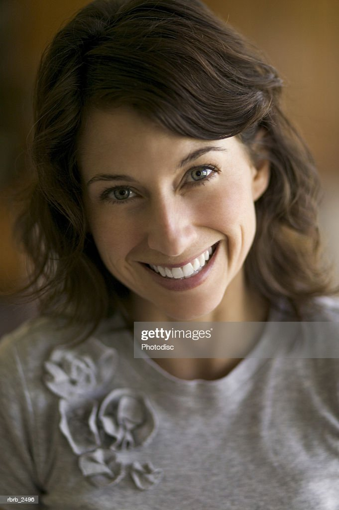 lifestyle portrait of an adult female brunette as she smiles at the camera : Foto de stock