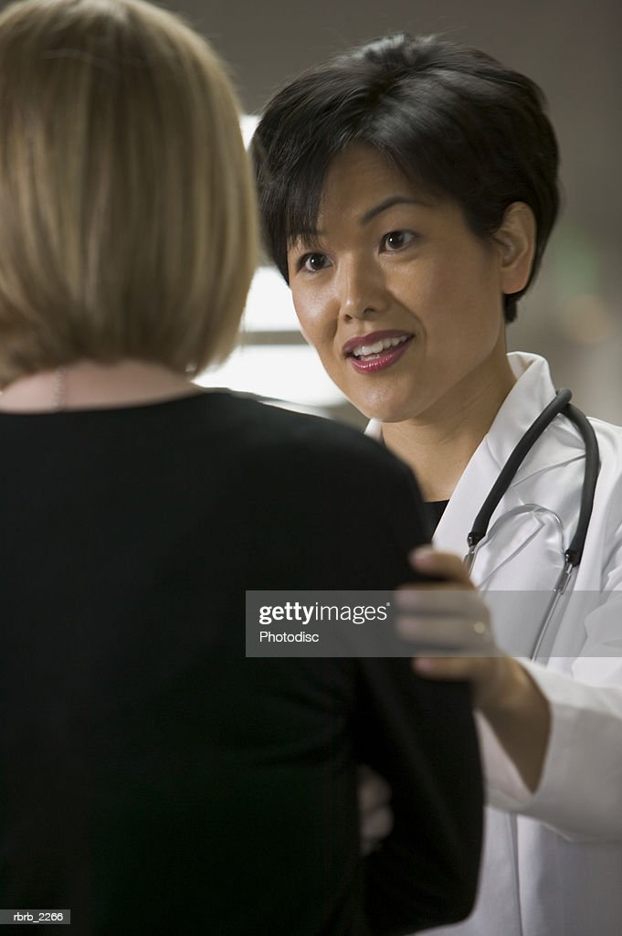 lifestyle portrait of an adult female doctor as she chats with an individual in the hallway : Foto de stock