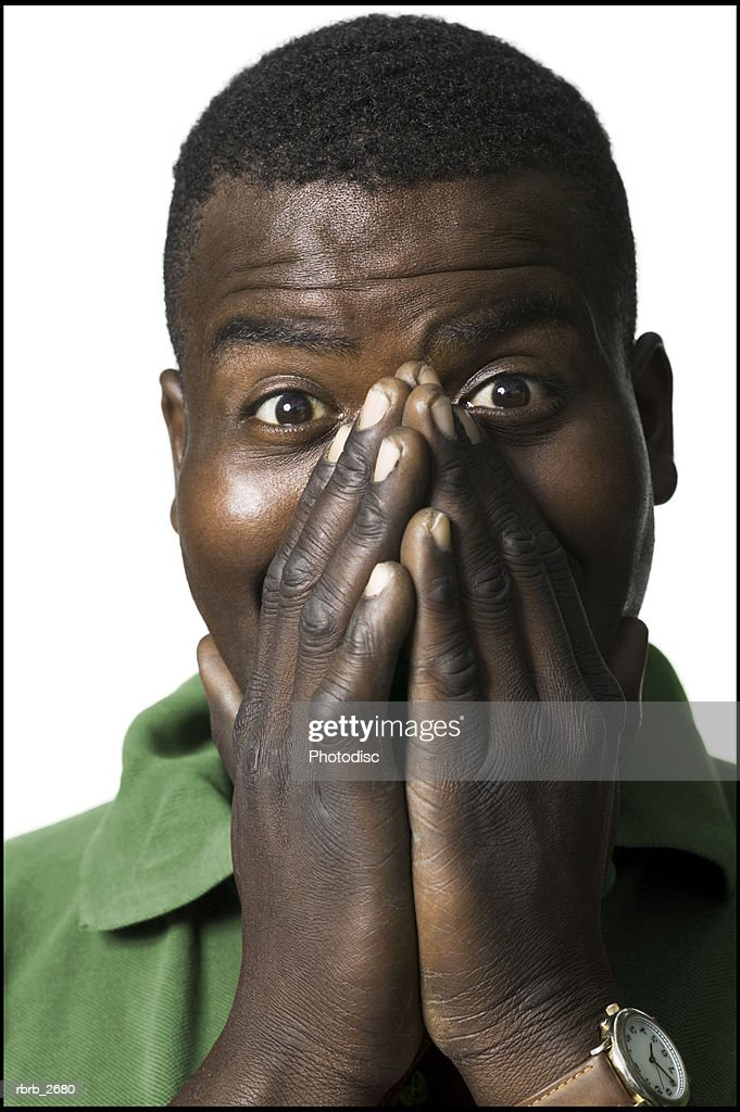 lifestyle portrait of an adult male in a green shirt as he puts his hands to his face in shock : Foto de stock
