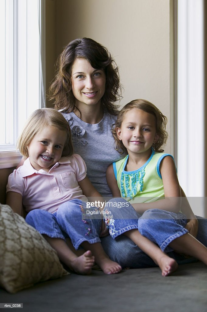 lifestyle portrait of an adult mother as she sits with her two young daughters : Foto de stock