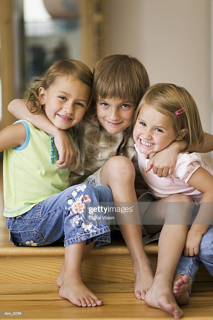 lifestyle portrait of three siblings as they put their arms around each other and smile : Stock Photo