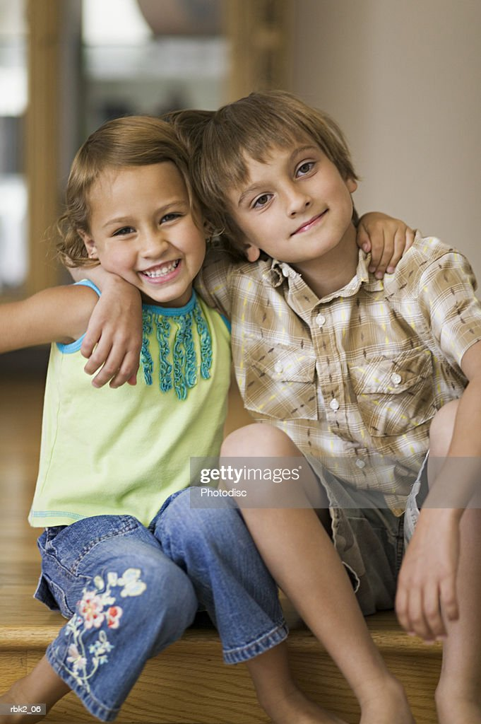 lifestyle portrait of two sibling children as they put their arms around each other and smile : Stock Photo