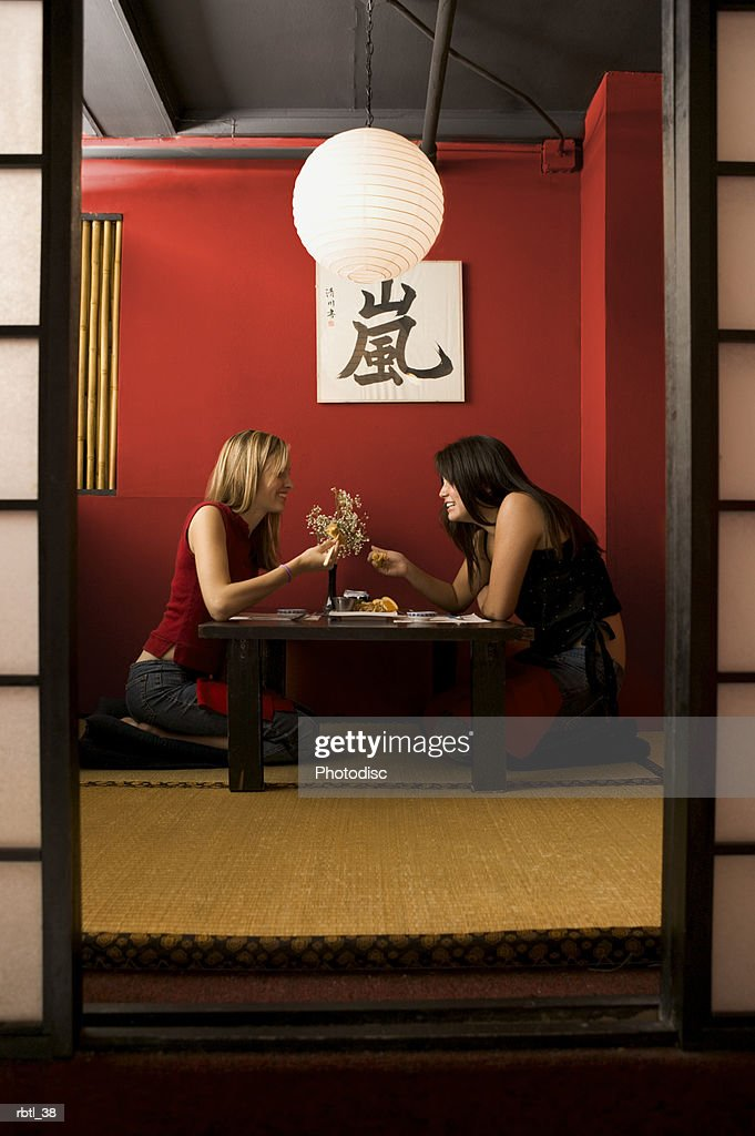 lifestyle portrait of two teenage female friends as they eat together in a restaurant : Foto de stock