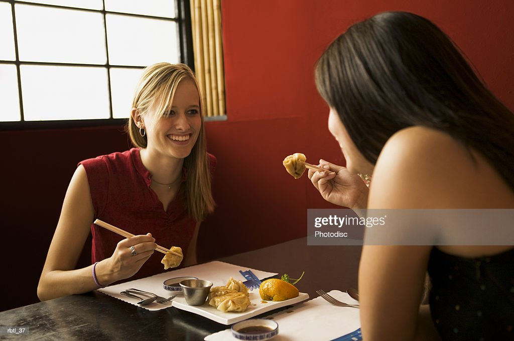 lifestyle portrait of two teenage females as they sit together and eat chinese food : Foto de stock