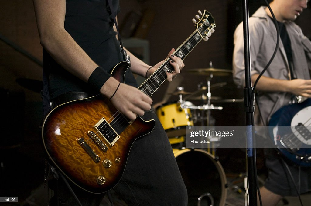 lifestyle portrait of two teenage males as they wildly practice their guitars with a band : Stockfoto