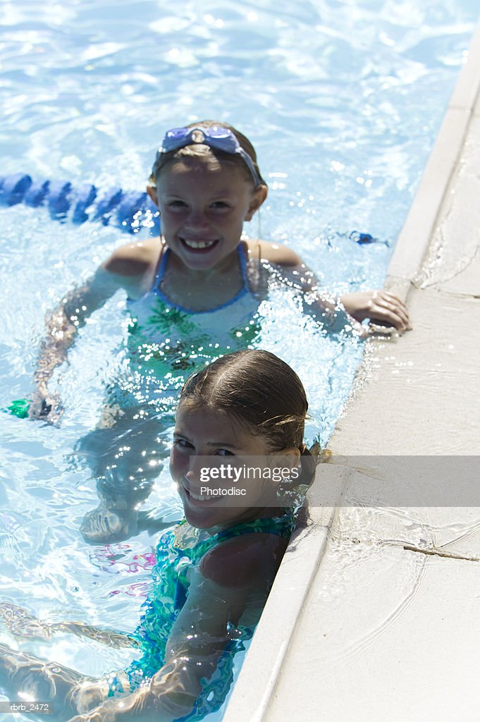 lifestyle portrait of two young female children as they both play in a swimming pool : Foto de stock