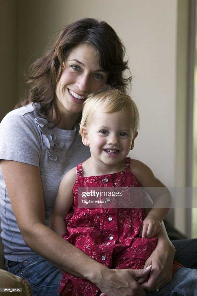 lifestyle portrait shot of an adult mother as she hugs her young daughter : Foto de stock
