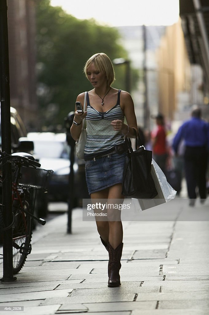 lifestyle shot of a blonde adult woman as she walks down the sidewalk using her cell phone : Foto de stock