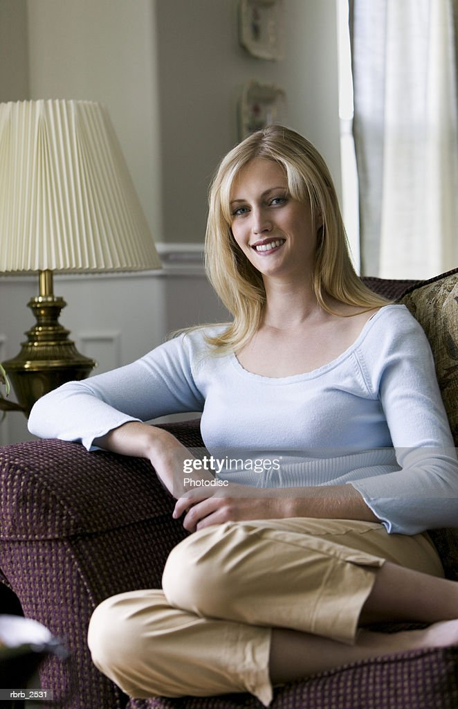 lifestyle shot of a blonde young adult woman as she sits on a couch and smiles : Foto de stock