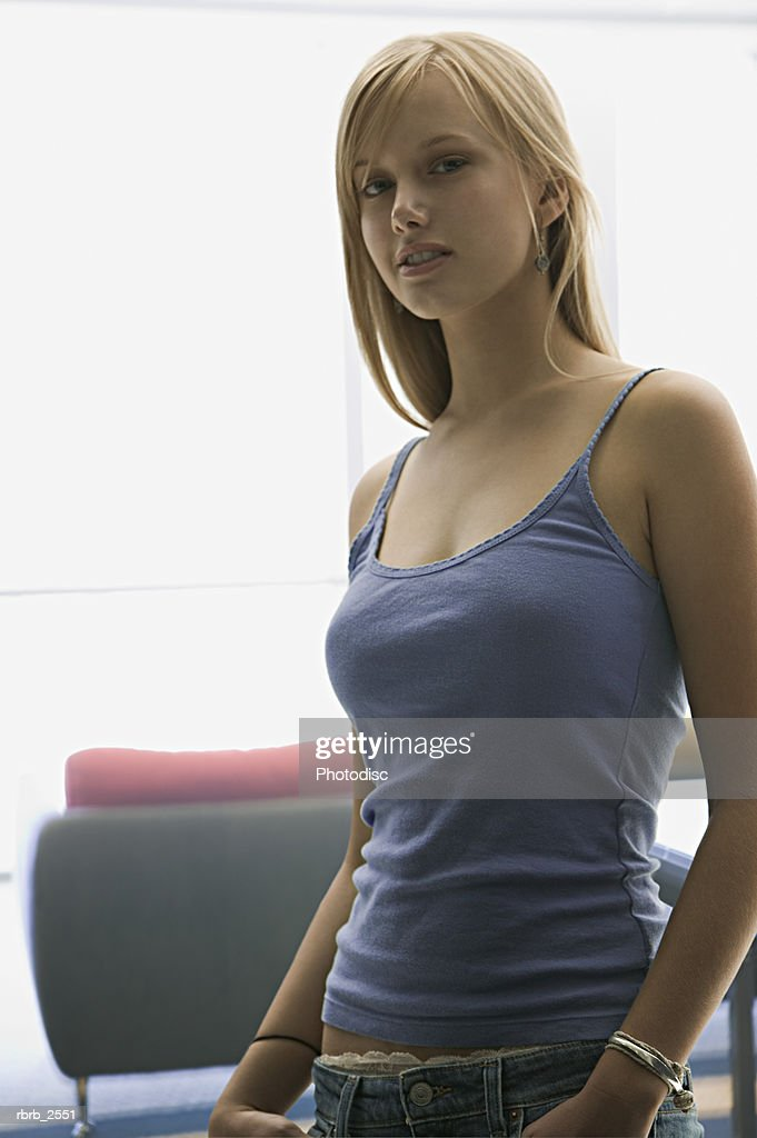 lifestyle shot of a blonde young adult woman in a purple tank top as she looks at the camera : Stockfoto