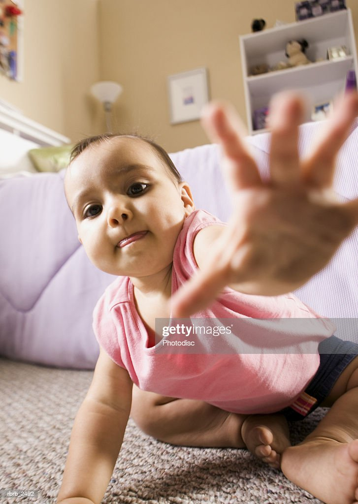 lifestyle shot of a female toddler in a pink shirt as she crawls and reaches for the camera : Foto de stock