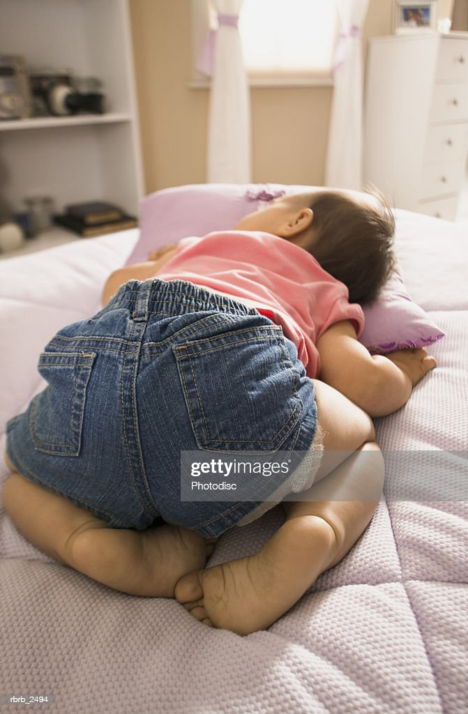 lifestyle shot of a female toddler in a pink shirt as she takes a nap on a bed : Foto de stock