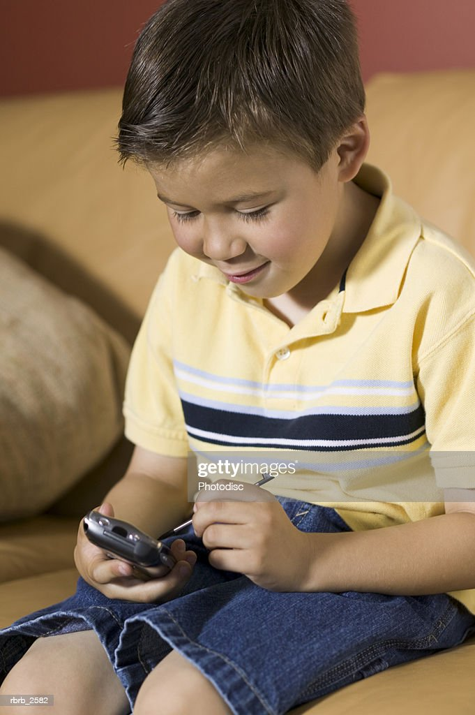 lifestyle shot of a male child as he sits on a couch and plays a video game on a pda : Stockfoto
