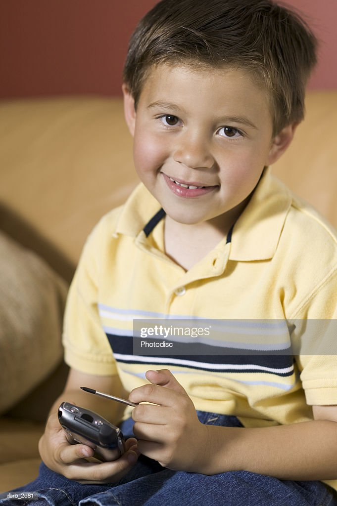 lifestyle shot of a male child as he sits on a couch and with a pda and smiles : Foto de stock