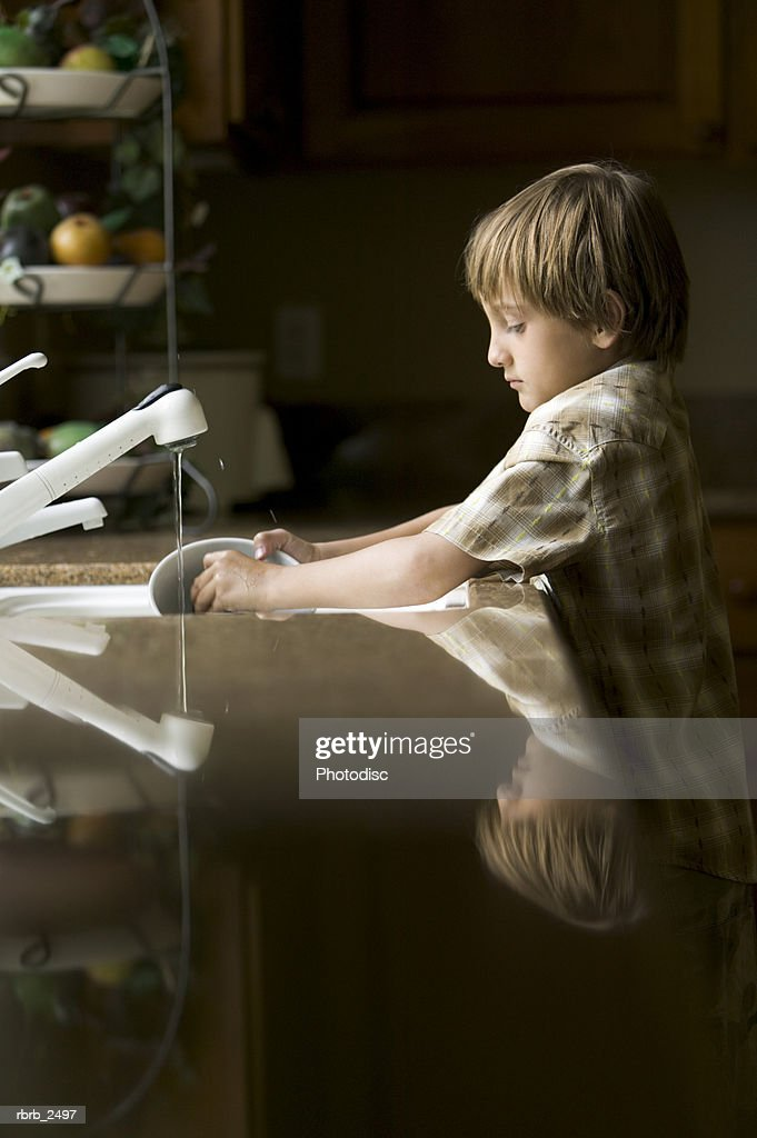 lifestyle shot of a male child as he washes dishes in the kitchen sink : Foto de stock
