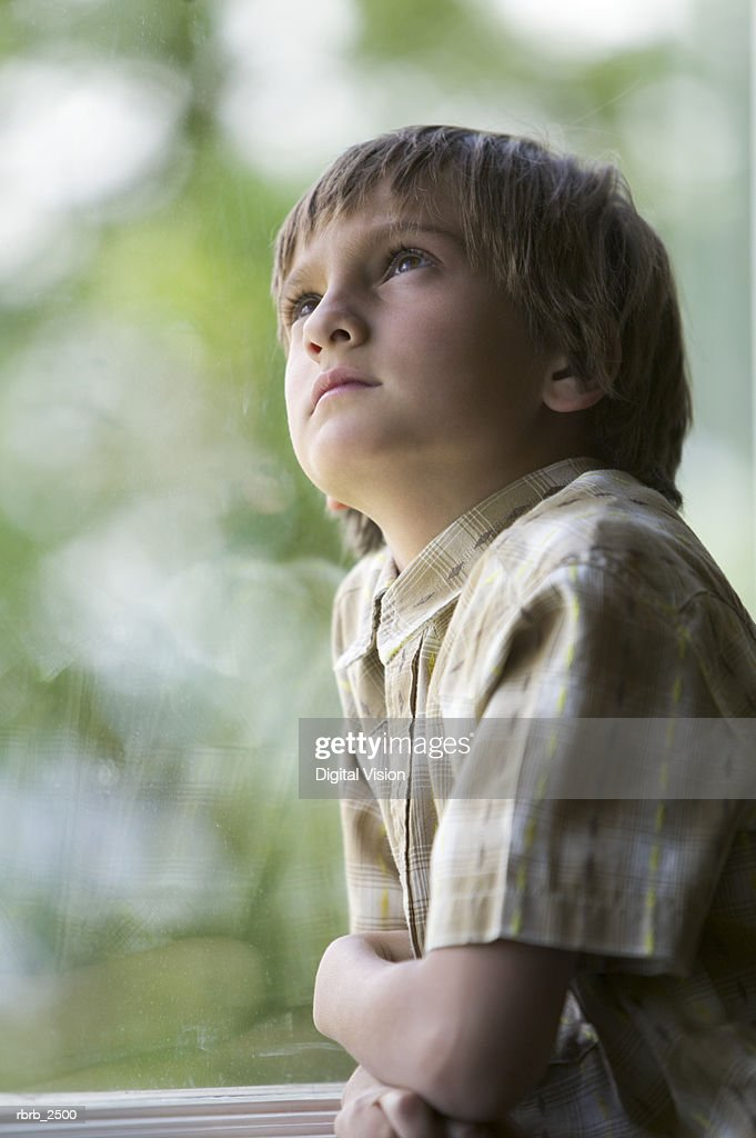 lifestyle shot of a male child in a plaid shirt as he stands by a window and glances upward : Foto de stock