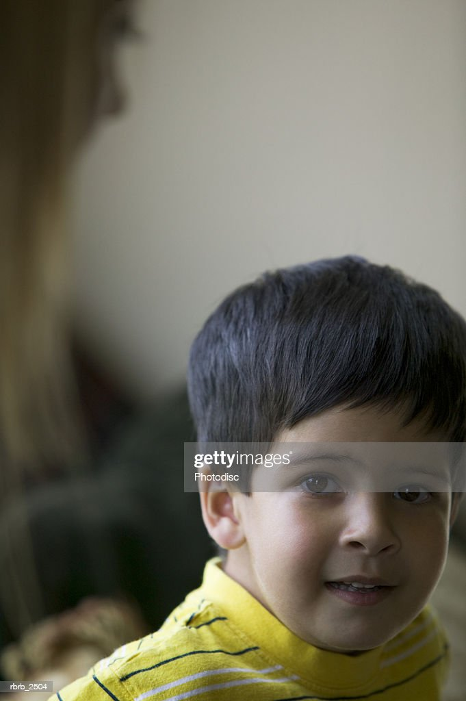 lifestyle shot of a male child in a yellow shirt as he looks at the camera : Foto de stock