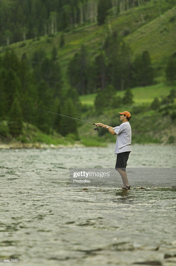 lifestyle shot of a male fisherman as he stands in a river bank and casts his rod : Foto de stock