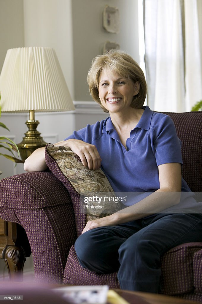 lifestyle shot of a mature adult woman as she sits on her couch and smiles : Foto de stock