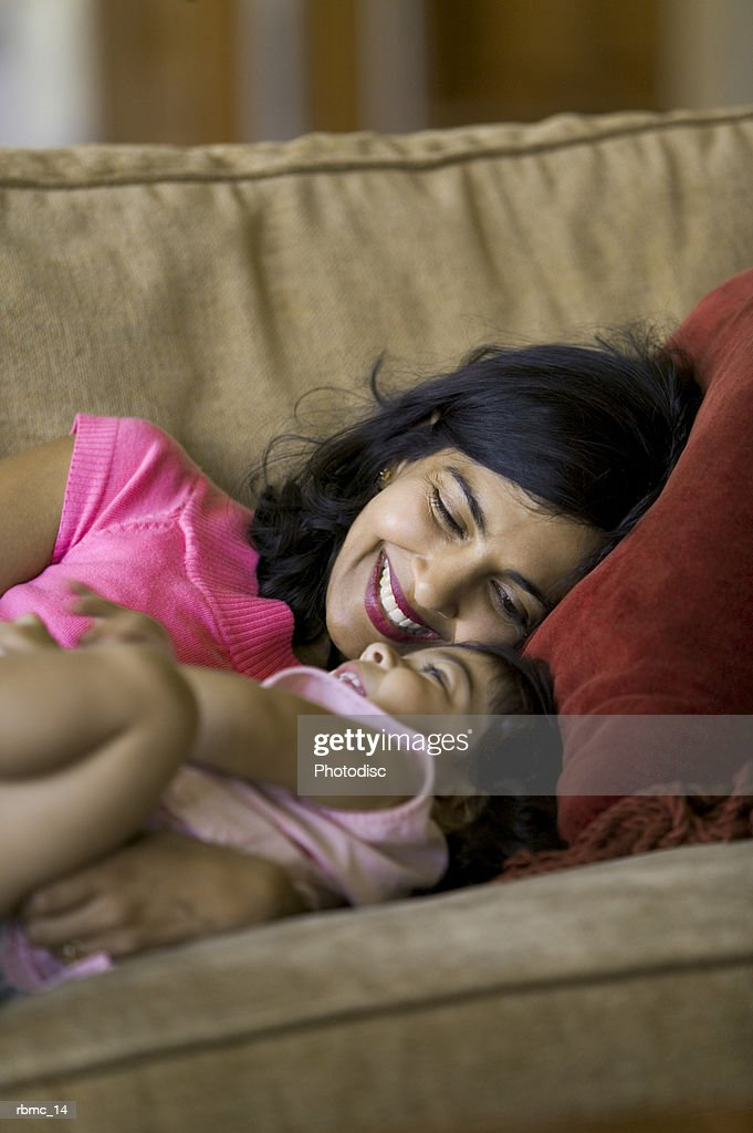 lifestyle shot of a mother as she lays on the couch and playfully tickles her toddler daughter : Stockfoto