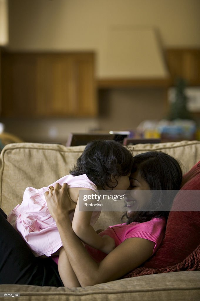 lifestyle shot of a mother as she lays on the couch and plays with her toddler daughter : Stockfoto