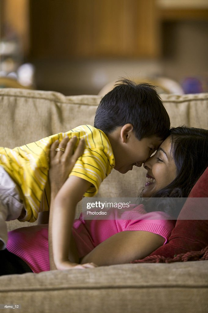 lifestyle shot of a mother as she lays on the couch and plays with her young son : Stockfoto
