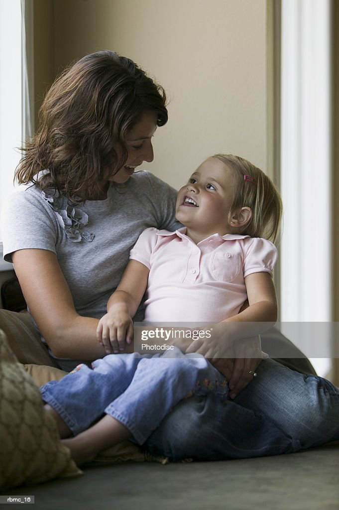 lifestyle shot of a mother as she sits on a couch and looks at her young daughter : Stockfoto